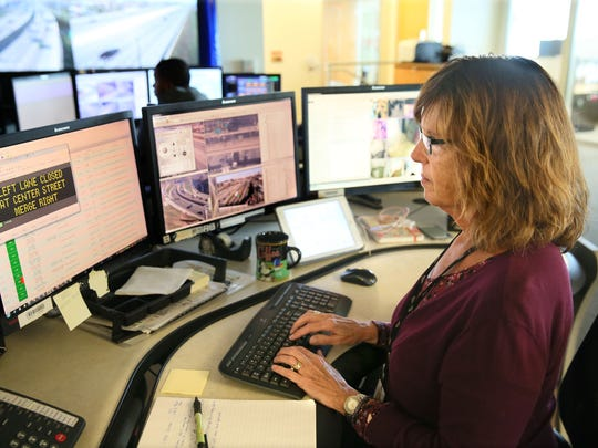 Melanie Pape, a control room operator in the State Traffic Operations Center, prepares Monday to put a notice on the electronic signs above the Milwaukee freeway.