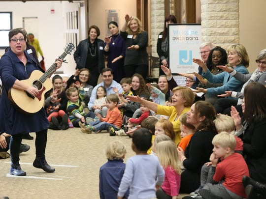 Music specialist Wendy Cohen plays her guitar and sings for children in the Jewish Community Center day care center Monday as parents and numerous elected officials take part.