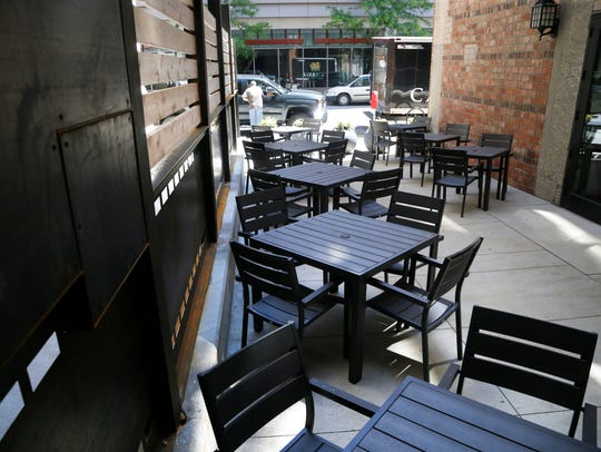 Patio tables sit ready for customers Thursday, May