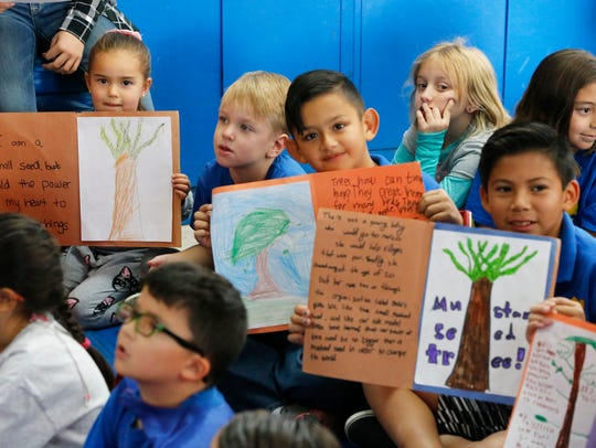 Children from El Paso Country Day School hold up posters