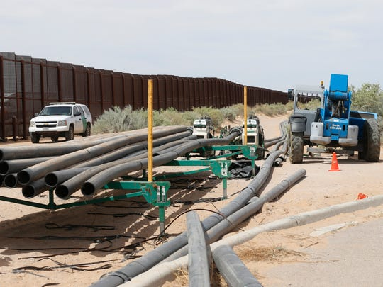 U.S. Border Patrol agents drive past construction materials that are being used to build the new border wall.