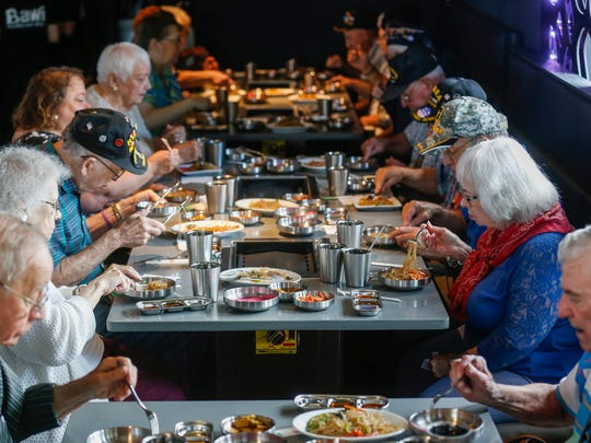 A group of Korean War veterans enjoy a meal during a special event at Bawi, a new all-you-can-eat Korean barbecue restaurant located at 4121 S. National Ave.