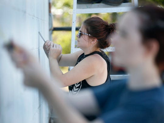 Alexandria Edwards, 18, from Holley, Orleans County, scrapes with others a wall before painting white to prep it for WALL\THERAPY 2018 at the Fedder Building.