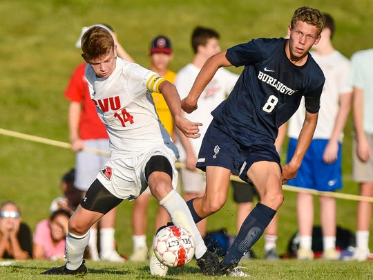 Champlain Valley Union's Nate Coffin, left, foots the ball in front of Burlington's Alex Dinklage in Hinesburg on Monday, September 18, 2017.