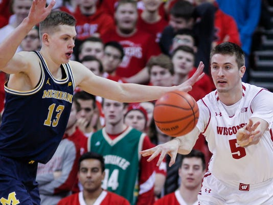 Wisconsin's Aaron Moesch (5) passes against Michigan's Moritz Wagner (13) during the first half of an NCAA college basketball game Sunday, Feb. 11, 2018, in Madison, Wis. (AP Photo/Andy Manis)