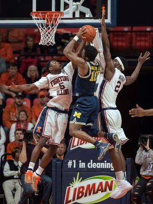 Michigan guard Derrick Walton Jr. (10) goes up between Illinois guard Jalen Coleman-Lands (5) and Illinois forward Kipper Nichols (2) during the first half Wednesday in Champaign, Ill.