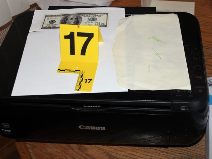 Photo of counterfeit money and printer