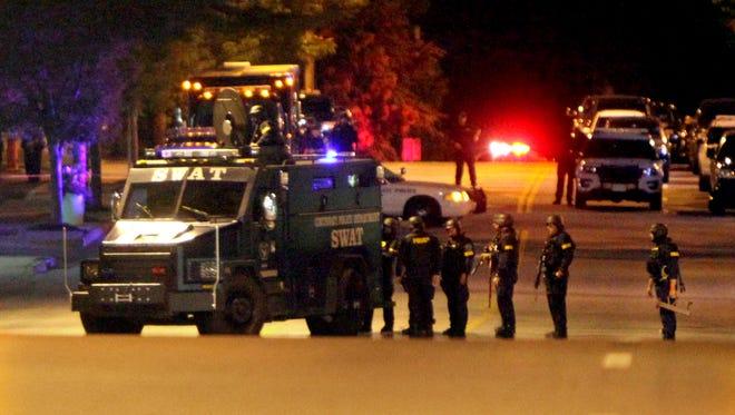SWAT officers assemble on Beechmont Avenue outside Scotty's Garage in June.