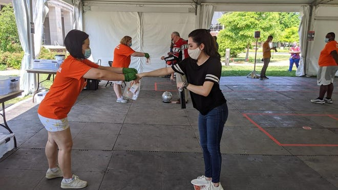 University of Illinois graduate student Kristen Muñoz submits her saliva sample for COVID-19 testing on the Urbana-Champaign campus.