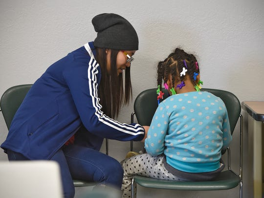 Chris Naw works with a homeless child Thursday, March 24, at the St. Cloud Salvation Army shelter as part of the SMART Kids program.
