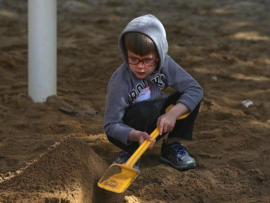 Julian Cuenca, 3, plays in the sand Tuesday during