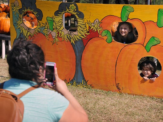 Susanna Morrow takes photos of her children, Kennedy,7, and Ethan Morrow, 4, Monday at Smith's Farms Pumkin Patch.
