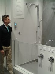 Nathan Caspers, Kohler Signature store manager, shows the Real Rain shower system that mimics rainfall.