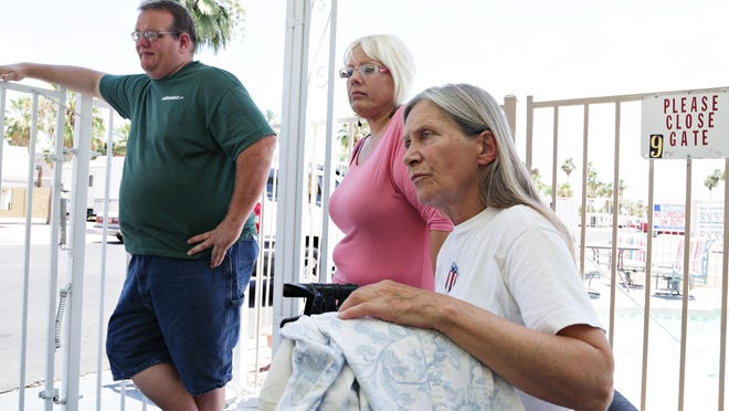 Resident Carlene Klebe, foreground, Glen Wacker, a resident, along with his friend, Dawn Green (in pink) at Tempe Travel Trailer Villa discuss the impending eviction of the RV Park's residents to make way for a 423 unit apartment complex along Apache Blvd. as seen in Tempe on June 11, 2015