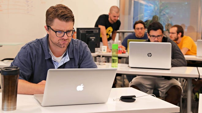 Ryan Taylor (left) works on a project at Rockit boot camp, a fast-track program, for Web development by offered by University of Phoenix.
