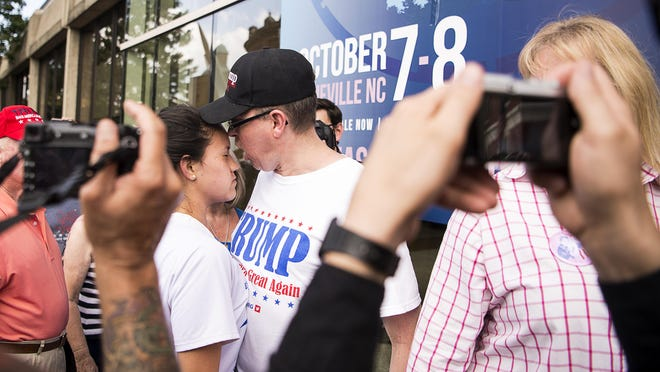 A Donald Trump supporter screams at a young protester, who did not wish to be identified, after she shouted profanity about Trump, while in line to enter the U.S. Cellular Center on Sept. 12.