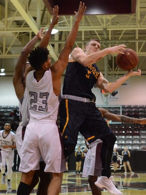 McMurry's Luke Stephenson (23) contests a layup by Howard Payne's Shadd Cole during the War Hawks' 83-80 win Tuesday at Kimbrell Arena.