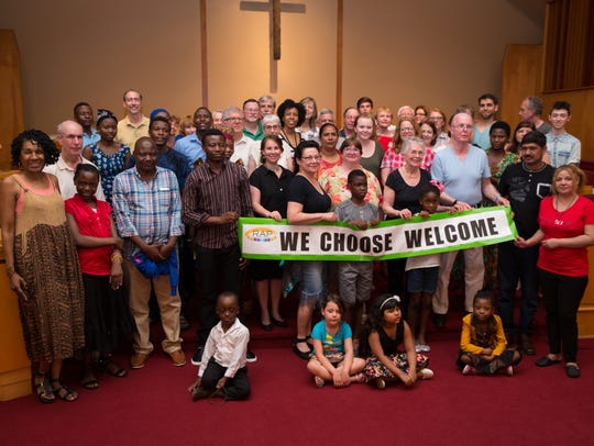 Refugee families and community members stand together