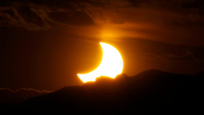 In this May 20, 2012, file photo, the annular solar eclipse is seen as the sun sets behind the Rocky Mountains from downtown Denver. The solar eclipse that is cutting a diagonal path across the U.S. next month is a boon for Missouri tourism. Some towns will have more visitors than residents on Aug. 21, 2017. Hotels and campsites are sold out as some communities are preparing for unparalleled numbers of visitors, all to observe about two minutes of near-darkness at the height of the day.
