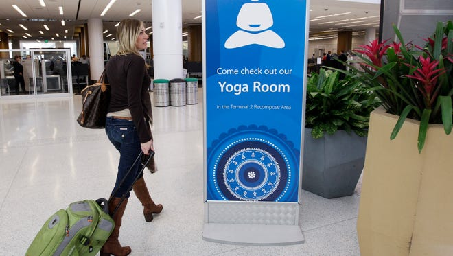 In this Friday, Jan. 27, 2012 photo, traveler Maria Poole leaves San Francisco International Airport's new Yoga Room after practicing in San Francisco. The quiet, dimly lit studio officially opened in a former storage room just past the security checkpoint at SFO's Terminal 2.