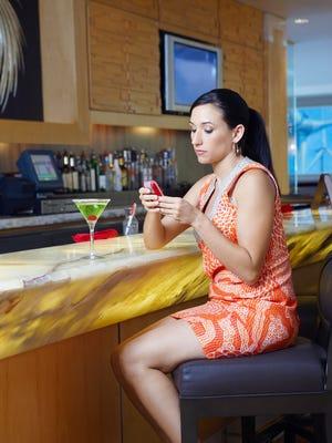A woman drunk texting at a bar.