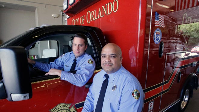 In this Thursday, June 30, 2016 photo, Josh Granada, left, and Carlos Tavarez, the first paramedic-firefighters to respond to the Pulse nightclub shooting, stand by their emergency vehicle at their fire station in Orlando, Fla. They made five trips with 13 victims to a hospital emergency room just a few blocks away the evening of the shooting.  (AP Photo/John Raoux)