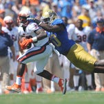Virginia Cavaliers running back Olamide Zaccheaus (33) runs the ball against the defense of UCLA Bruins linebacker Myles Jack (30) during the first half at the Rose Bowl.