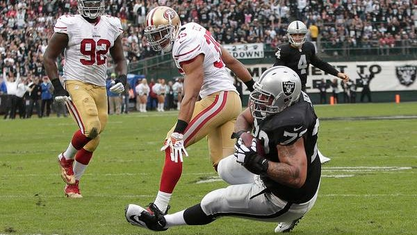 Oakland Raiders tackle Donald Penn (72) scores on a 3-yard touchdown pass from quarterback Derek Carr (4) in front of San Francisco 49ers safety Eric Reid (35) and defensive end Quinton Dial (92) during the second quarter Sunday, Dec. 7, 2014.