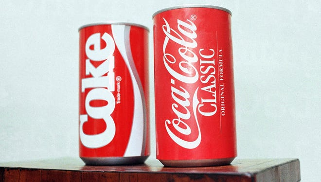 In this July 11, 1985, file photo, cans of New Coke and Coca-Cola Classic are on display during a news conference in Atlanta. New Coke's sweeter formula was  marketed as an improved replacement for the flagship soda, but the outcry was immediate and sustained. Coke tried to sell both versions for awhile, but eventually reverted to Coca-Cola Classic.