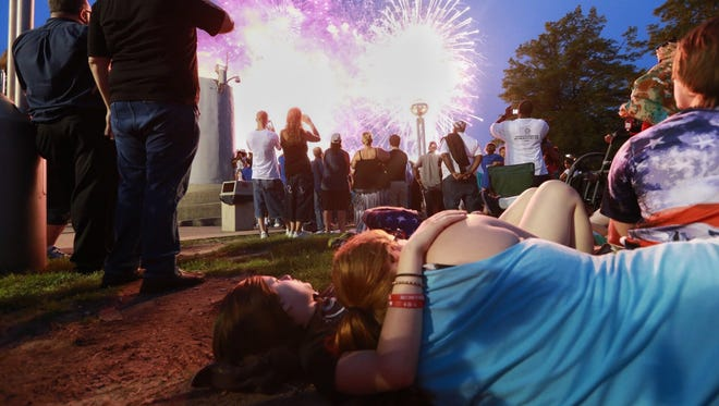 Selena Calderon (left) of Dearborn and Emilie Fritts of Southgate watch the grand finale during the Ford Fireworks festival at Hart Plaza in downtown Detroit on Monday June 22, 2015.