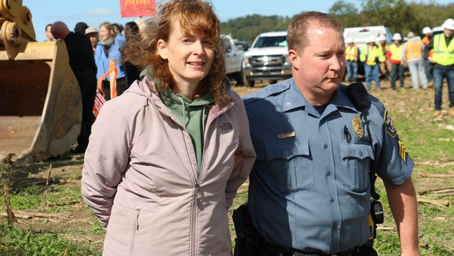 A woman is taken away in handcuffs by a police officer after a protest at a pipeline construction site in Lancaster County on Monday.