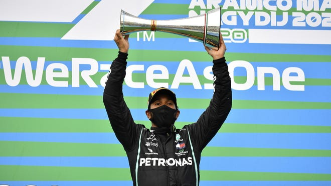 Mercedes driver Lewis Hamilton of Britain celebrates on the podium after winning the Hungarian Formula One Grand Prix at the Hungaroring racetrack in Mogyorod, Hungary on Sunday.