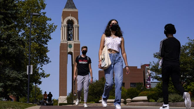 Masked students walk Sept. 10 through the campus of Ball State University in Muncie, Ind. Out of nearly 600 students tested for the virus at Ball State, more than half have returned been found positive, according to data reported by the school.