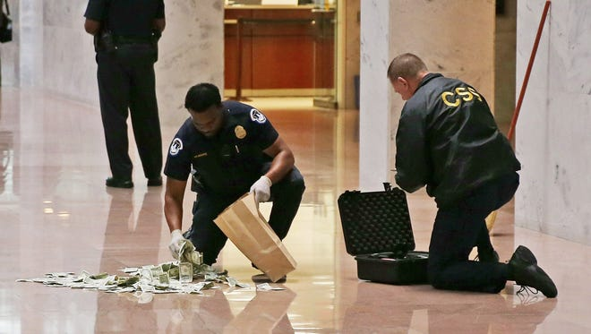 Capitol Police officers clean up money that was thrown on the floor last Wednesday by demonstrators protesting against the partial federal government shutdown.
