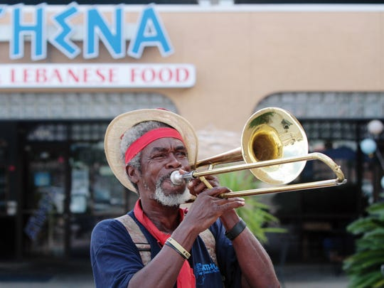 John Mills, a.k.a. John the Revelator, plays slide trombone to entertain and attract customers to Athena's in this Advertiser file photo.