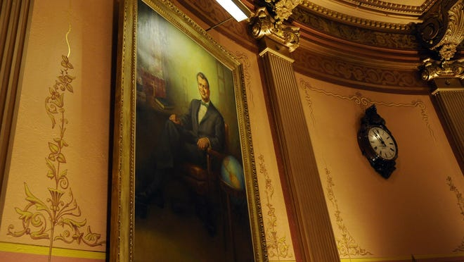 """A portrait of former Gov. G. Mennen """"Soapy"""" Williams is seen at the Capitol in Lansing on Tuesday. An image of his signature achievement, the Mackinac Bridge, is seen in the background of the portrait, beginning a tradition of symbolism in gubernatorial paintings at the Capitol."""