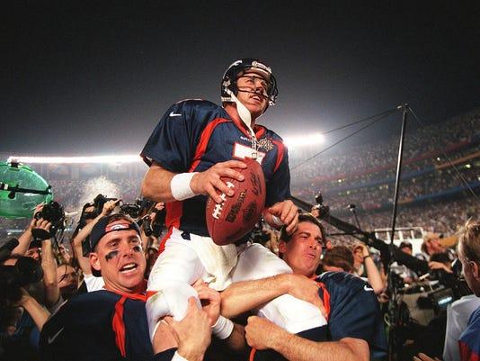 Denver Broncos quarterback John Elway (C) is carri
