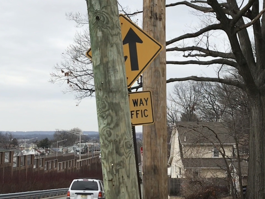 Unused utility pole obscures two-way street sign on