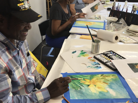 Charlie Hunt works on a watercolor painting at the