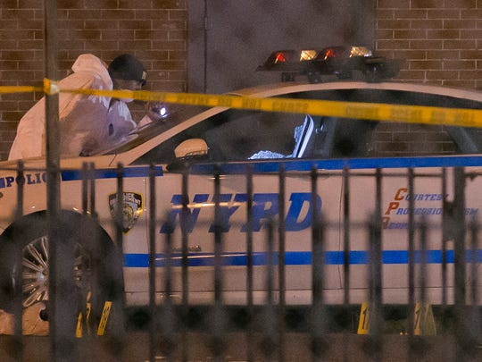 Investigators work at the scene where two NYPD officers were shot Dec. 20, 2014 in the Bedford-Stuyvesant neighborhood of the Brooklyn borough of New York.