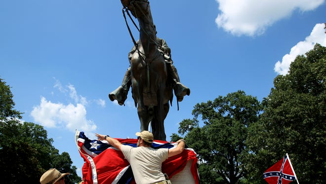 In this July 12, 2015, file photo, Mike Goza, left, helps Mike Junor drape a Confederate battle flag over the base of the statue and tomb of Nathan Bedford Forrest, a rebel general, slave trader and early Ku Klux Klan member, at Health Sciences Park in Memphis, Tenn. State House members said they were surprised that they unwittingly passed a resolution honoring Forrest on April 13, 2017.