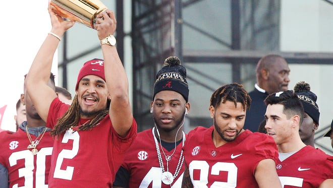 Alabama quarterback Jalen Hurts, left, holds up the national championship trophy during the NCAA college football championship celebration, Saturday, Jan. 20, 2018, in Tuscaloosa, Ala. Alabama won the national championship game against Georgia 26-23 in overtime. (AP Photo/Brynn Anderson)