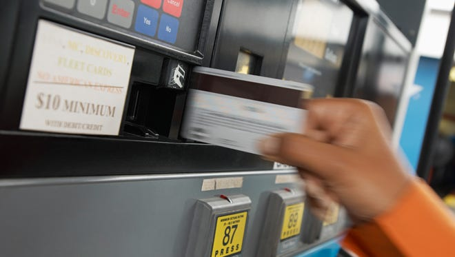 Paying with credit card at gas pump.