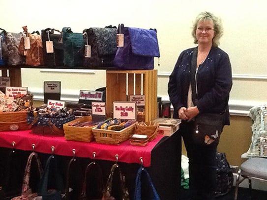 Lauren Ferguson of LaMa Bags stands next to her booth