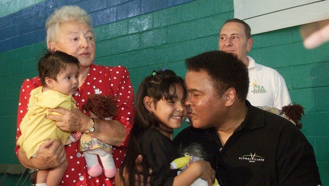5/8/2000: Former heavyweight champion Muhammad Ali gives a kiss to one of the many children that were on hand at the Gynasio Kiki Munoz in the Colonia Revolucion along with Suzie Valadez, a local missionary who runs the Hands of Love and Hope Mission.