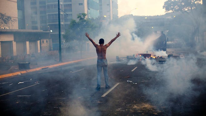 A demonstrator raises his arms toward the Bolivarian National Police (BNP) firing tear gas and a water canon in the Altamira neighborhood of Caracas, Venezuela, Feb. 19, 2014.