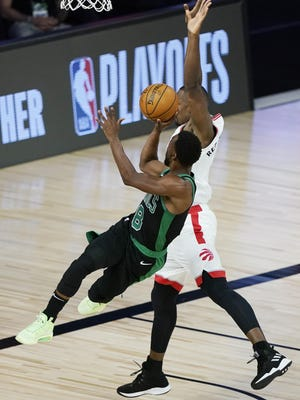 Celtics guard Kemba Walker shoots against the Toronto Raptors' Serge Ibaka during the first half in Game 1 of their semifinal playoff series Sunday in Lake Buena Vista, Fla. Walker scored 18 points and had 10 assists in the Boston victory.