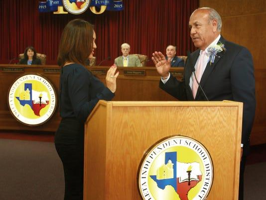 VICTOR CALZADA-EL PASO TIMES New YISD school board trustee Mike Rosales took his oath of office from granddaughter Arika Mais Monday.