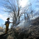 Jordan Campbell, of the Dresden Volunteer Fire Department, uses a water canister to put out a recent roadside brushfire in Frazeysburg.