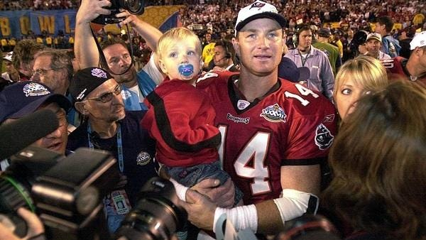 Former FSU quarterback Brad Johnson holding his son after Johnson helped lead the Tampa Bay Bucs to a win over the Oakland Raiders in Super Bowl XXXVIII in 2003.